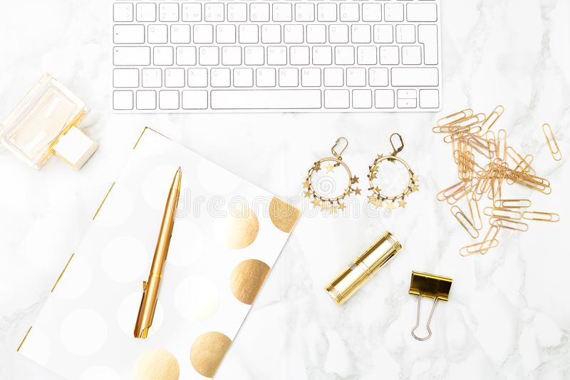Keyboard and of office items of gold color and cosmetics on the. Desktop royalty free stock images