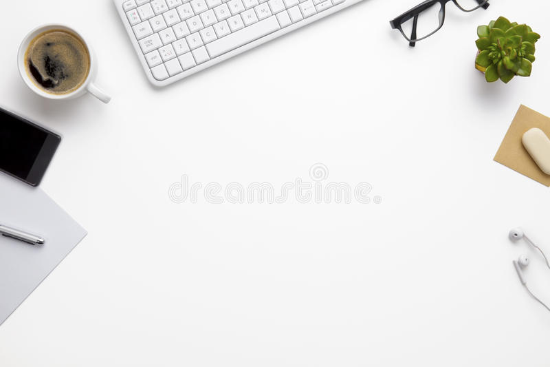 Keyboard With Office Supplies On White Desk. Overhead view of computer keyboard with office supplies on white desk royalty free stock image