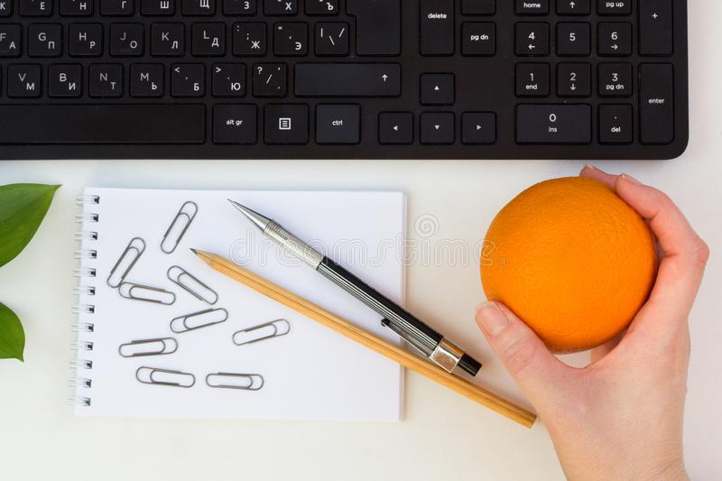 Keyboard, pencil, notebook, paper clips, orange. The concept. Of the workplace stock photo