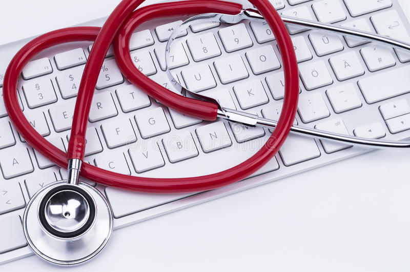 Keyboard and stethoscope. Image shows a red stethoscope at a computer keyboard stock image