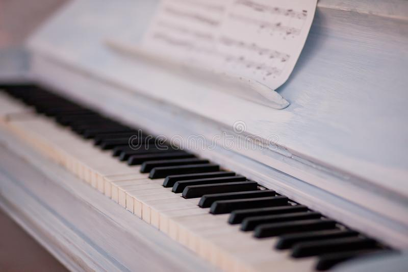 Keyboard of white vintage piano with black and white key and sheet music royalty free stock image