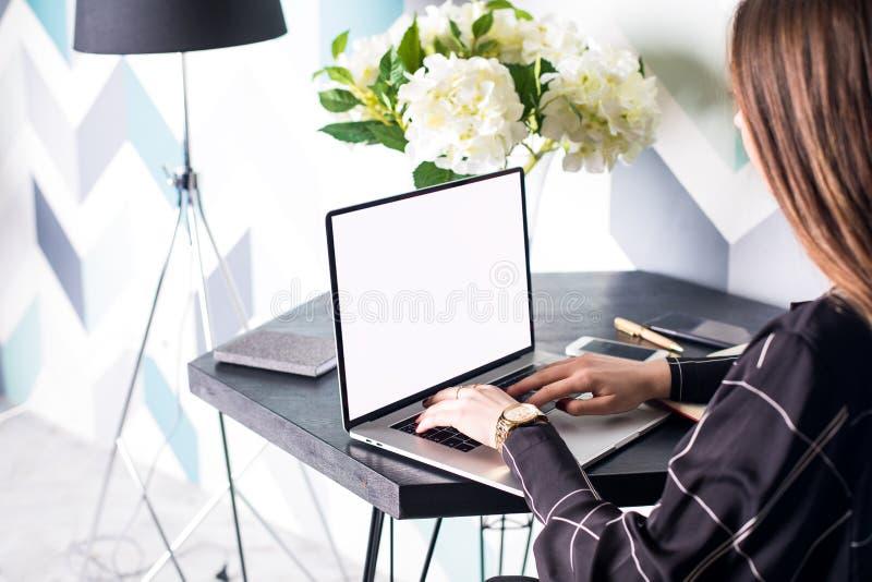 Keyboarding för författare för socialt massmedia för Hipsterflickafrilans nöjd på den moderna bärbara netto-boken med den tomma k fotografering för bildbyråer