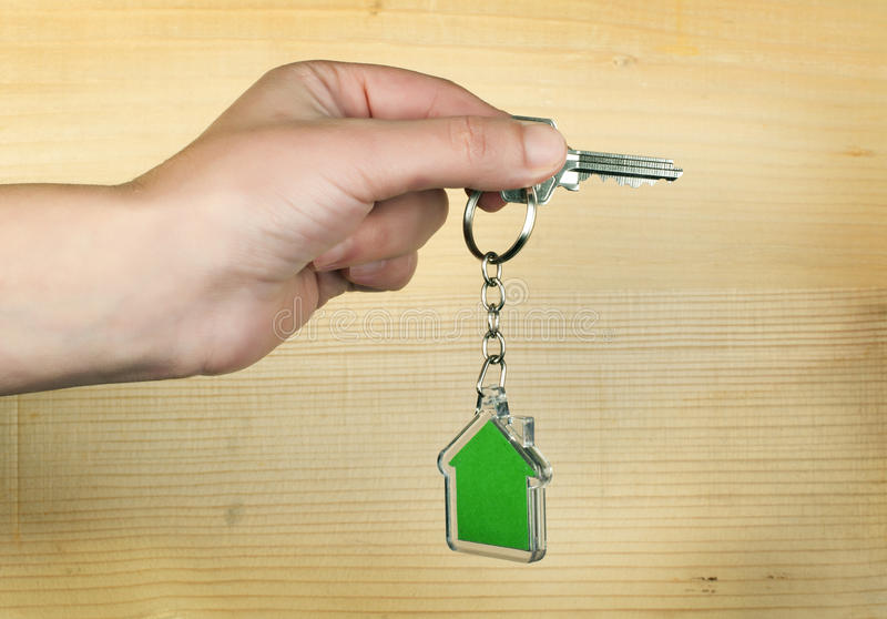 Keychain with figure of green house. Hand holding key and Keychain royalty free stock photo