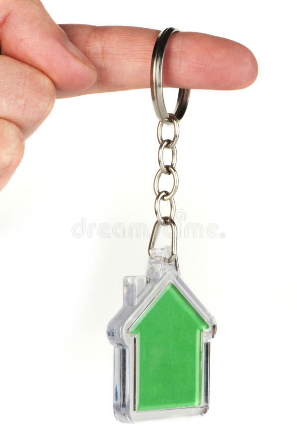 Keychain with figure of green house. Hand holding key and Keychain stock image