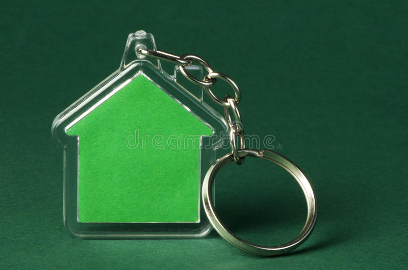 Keychain with figure of green house. On green background stock images