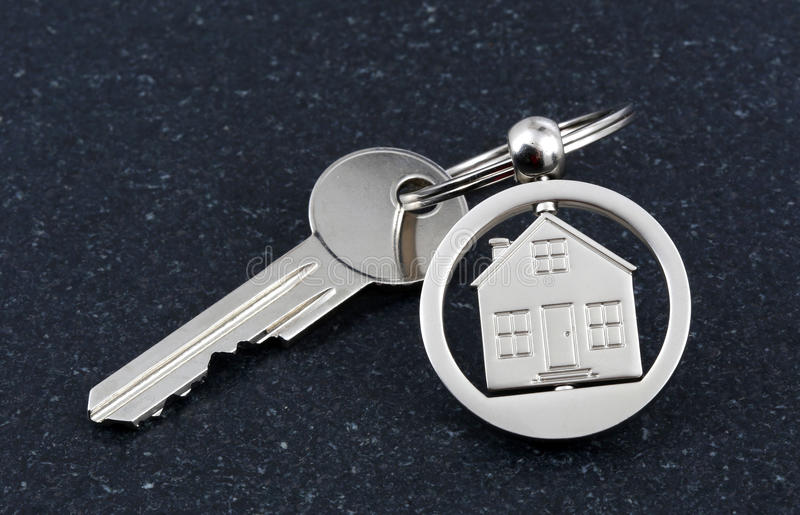 Keychain figure of house and key. On stone table royalty free stock image
