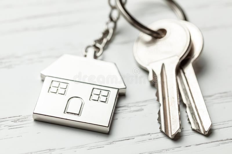Keychain house and keys on white wooden background.  stock image