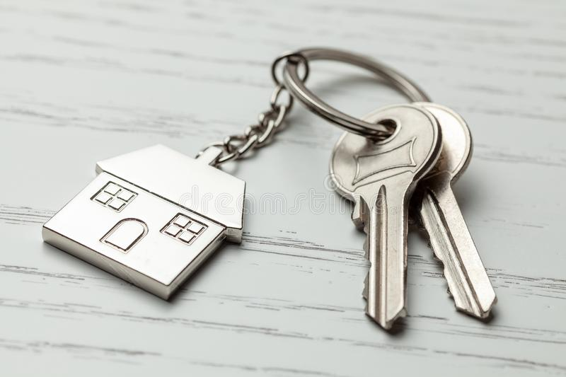 Keychain house and keys on white wooden background stock photography