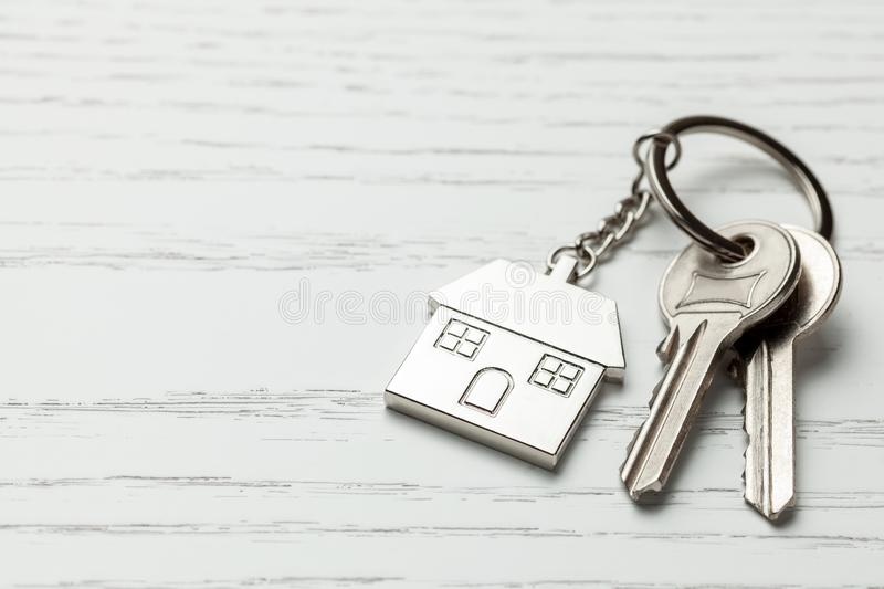 Keychain house and keys on white wooden background. Copy space for text. stock photo