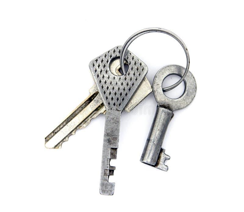 Keychain von drei alten Stahlschlüsseln von Vorhängeschlössern auf Ring auf weißem Ba lizenzfreie stockbilder