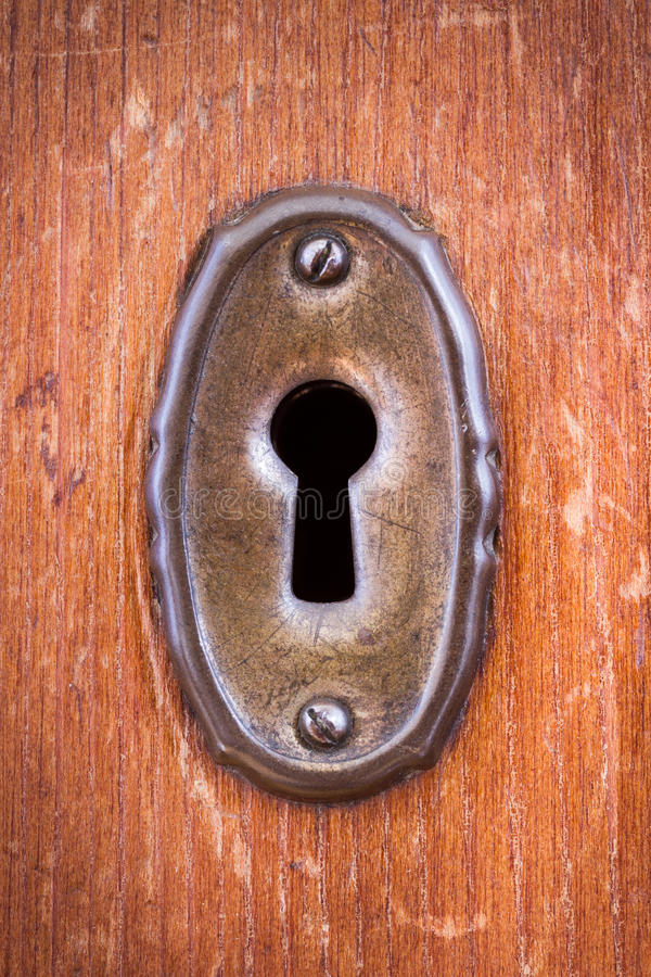 Keyhole. Close-up shot of a scratched keyhole on a wooden door stock image