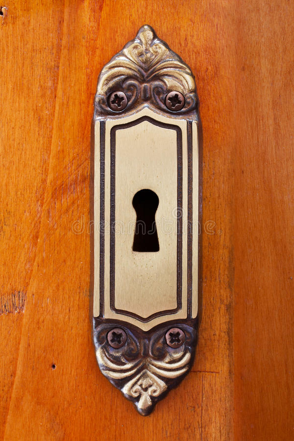 Keyhole. Close-up shot of a keyhole on a wooden door royalty free stock photos