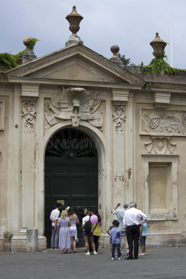 Keyhole of the Villa Magistrale dei Cavalieri di Malta Rome Ital. ROME, ITALY - JULY 23, 2016: line of tourists waiting to look through the keyhole of the Villa stock photos