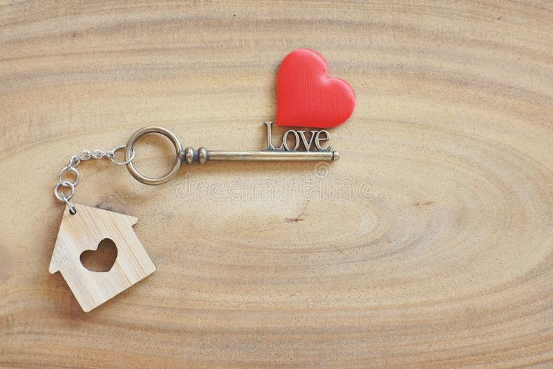 Keyring da casa e chave da forma do amor na tabela de madeira do vintage Decorado com mini coração como o presente doce para o am imagens de stock royalty free