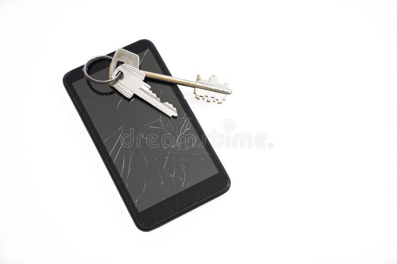 Keys on black mobile phone with a broken screen royalty free stock photo