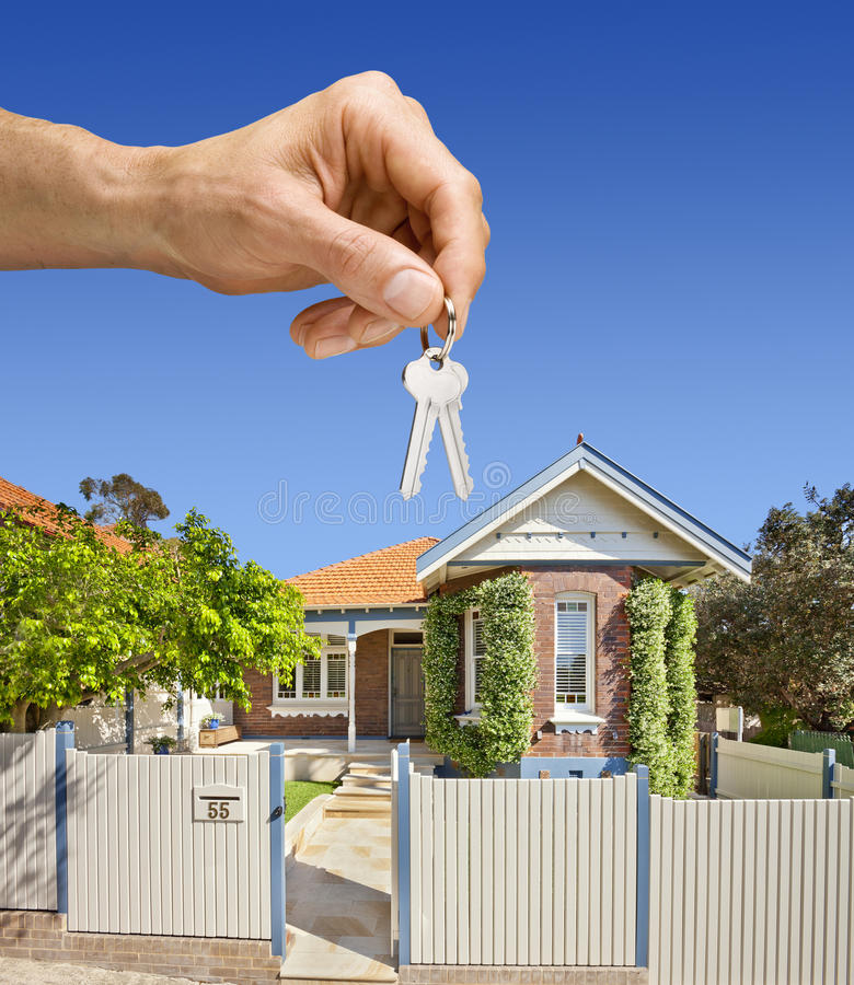 Keys Home House Sale Sales Property. A hand holding house keys with a house in the background. A typical Australian federation home built circa 1910 in Sydney stock photo