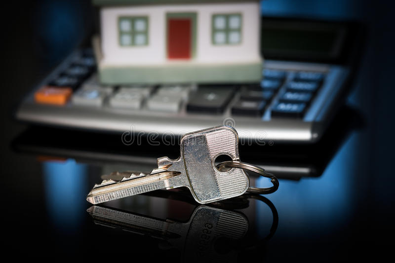 Keys with house and calculator. House over white with calculator and house keys stock photo
