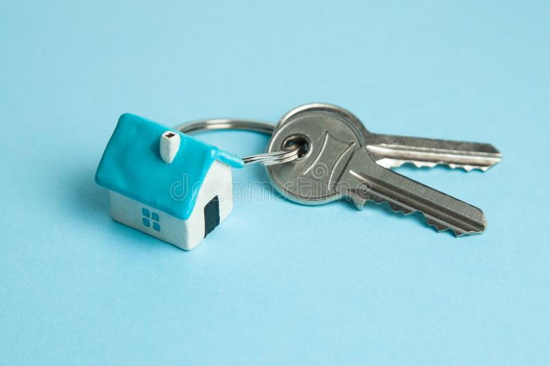 Keys and a keychain house on a blue background. Concept of buying a house. Renting, mortgage, gift royalty free stock image