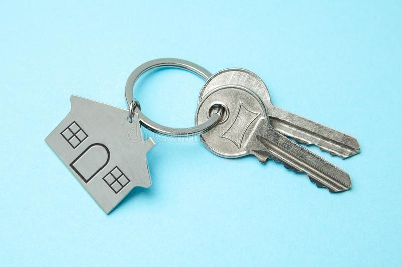 Keys and a keychain house on a blue background. Concept of buying a house, renting stock photography
