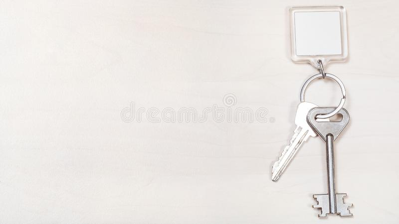 Keys on keyring with blank white keychain on board. Two door keys on keyring with blank white keychain on panoramic pale brown board royalty free stock image
