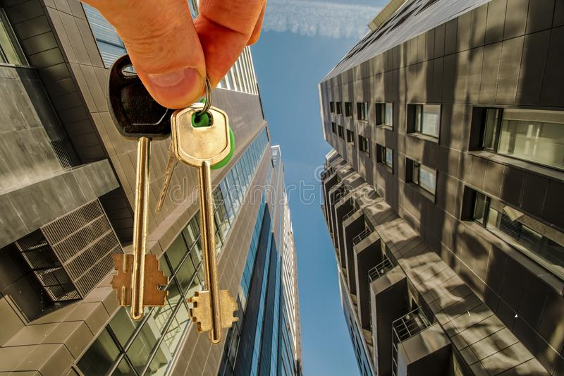 The keys to the apartment in the background of the facade of the house . Тhe concept of sales in the real estate market royalty free stock photography