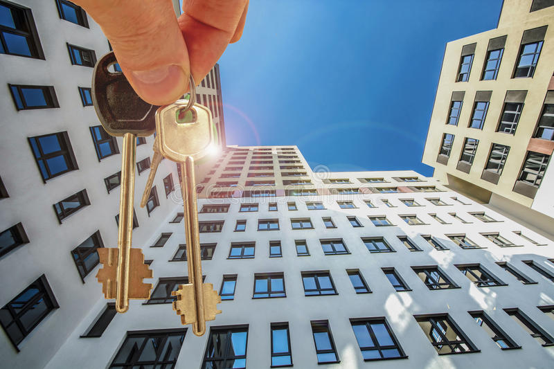The keys to the apartment in the background of the facade of the house . Тhe concept of sales in the real estate market royalty free stock images