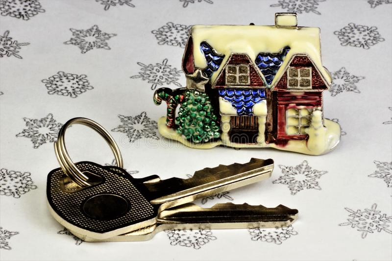 The keys to the Christmas house are a symbol of festive well-being. The key to the house on the background of winter snowflakes, a. Successful purchase of the royalty free stock photo