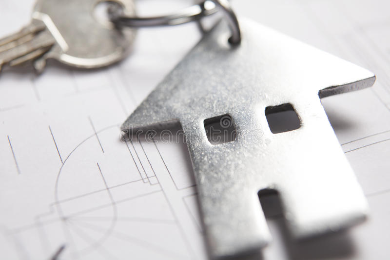 Keys To Home On Architects Plans With House Shaped Keyring. Close Up Of Keys To Home On Architects Plans With House Shaped Keyring royalty free stock photo