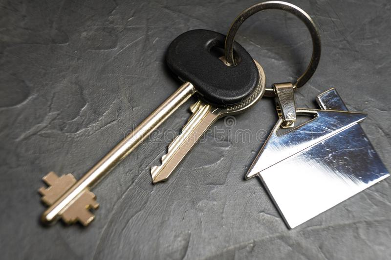 Keys to the house with a keychain in the shape of the house stock photos