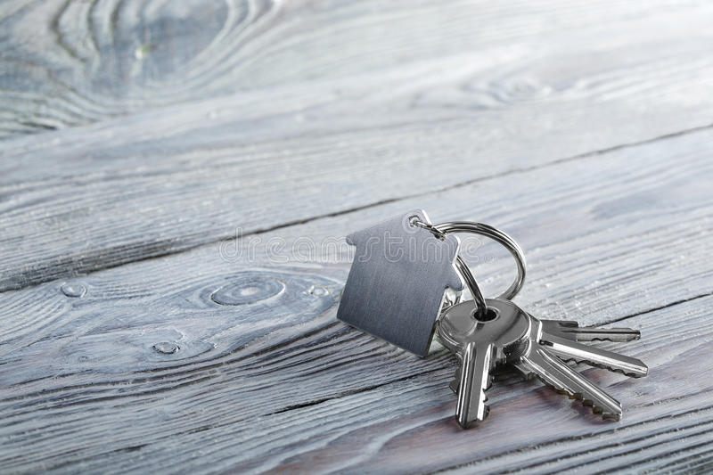 Keys to house with keychain on white wooden background. Keys to house with keychain on a white wooden background stock images