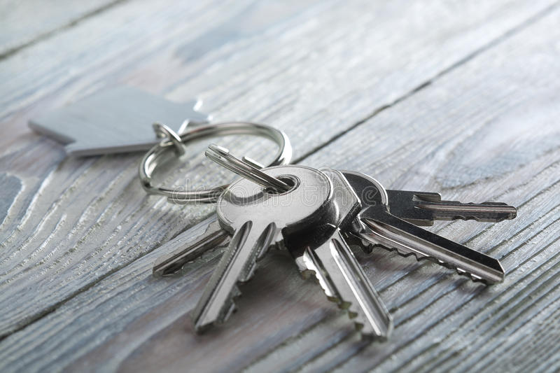 Keys to house with keychain on white wooden background. Keys to house with keychain on a white wooden background stock photos