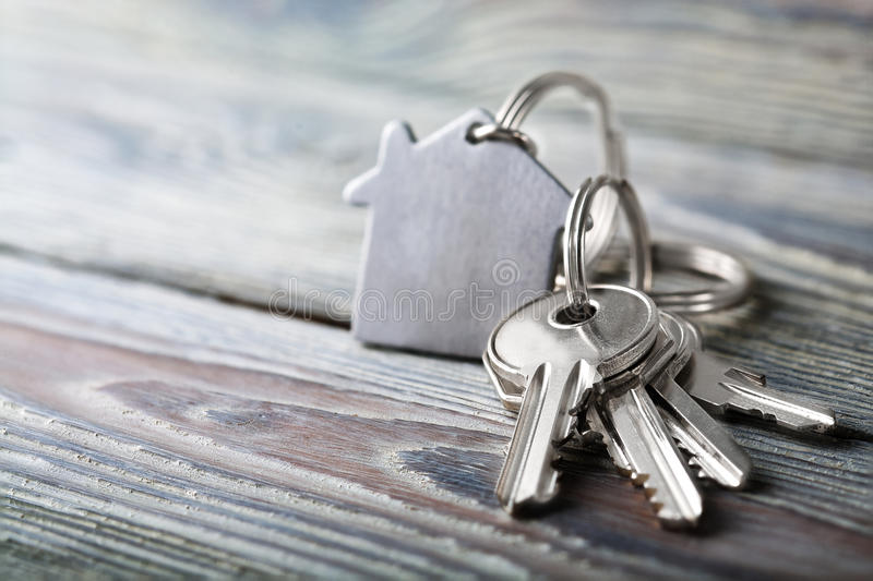 Keys to house with keychain on white wooden background. Keys to house with keychain on a white wooden background stock photo