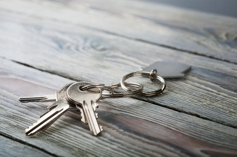 Keys to house with keychain on white wooden background. Keys to house with keychain on a white wooden background royalty free stock photos