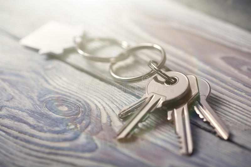 Keys to house with keychain on white wooden background. Keys to house with keychain on a white wooden background stock image