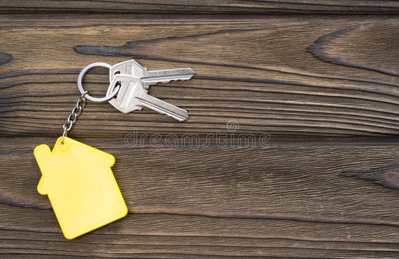 Keys to housing with a keychain in the form of a house on a wooden background. royalty free stock photo