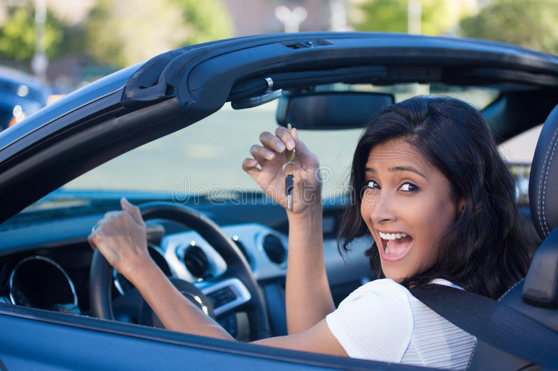 Keys to my new car. Closeup portrait, young cheerful, joyful, smiling, gorgeous woman holding up keys to her first new sports car. Customer satisfaction stock image