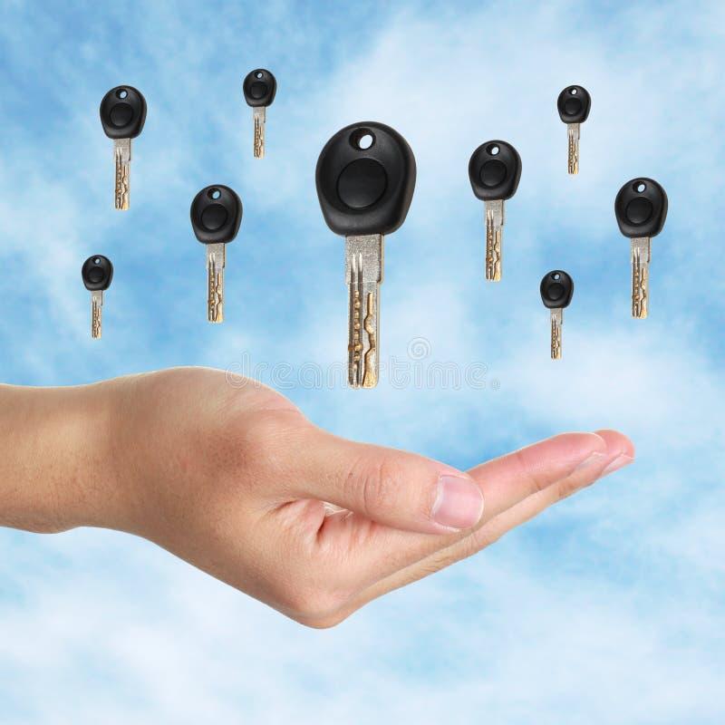 Keys to success. Hand open and many keys falling from the sky royalty free stock photo