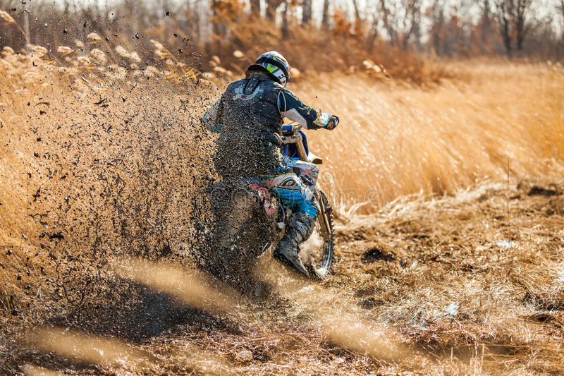 KHABAROVSK, RUSSIA - OCTOBER 23, 2016: Enduro bike rider on a field with dry grass in autumn. The motorcycle skids and makes a lo stock images