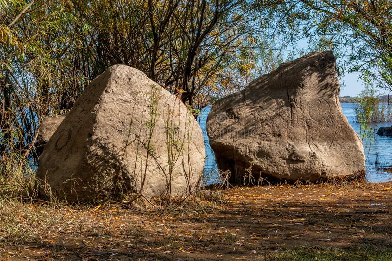 Ancient petroglyphs carved on stones on the bank of the Amur River near the. KHABAROVSK, SIKACHI-ALYAN, RUSSIA, 29 SEPTEMBER 2018: Ancient petroglyphs carved on royalty free stock photos
