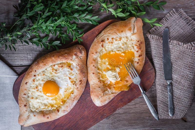 Khachapuri in Adzharian met Adyghe-kaas, kaas en dooier Traditioneel Kaukasisch voedsel stock foto's