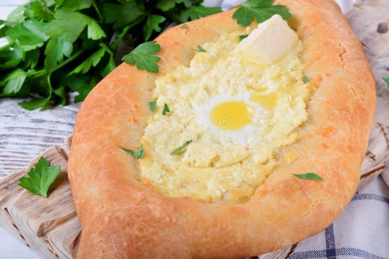 Khachapuri de Adjarian de la pasta de levadura con queso del sulguni, el huevo de codornices y la mantequilla imágenes de archivo libres de regalías