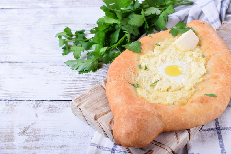 Khachapuri de Adjarian de la pasta de levadura con queso del sulguni, el huevo de codornices y la mantequilla imagen de archivo libre de regalías