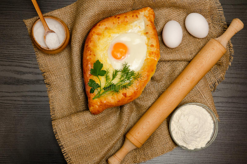 Khachapuri with eggs on sackcloth, flour, eggs and salt on black table.  royalty free stock images