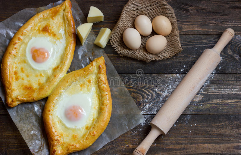 Khachapuri on flour, eggs and rolling pin on black table, top view royalty free stock photos