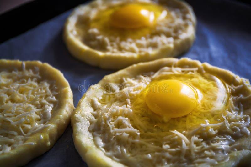 Khachapuri från rismjöl, kesodeg med ägget och mozzarellaost stekhet f?rberedelse ovanf?r sikt fotografering för bildbyråer