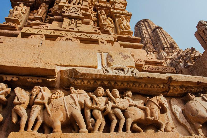 Khajuraho temple reliefs, India. Artworks on walls of 10th century temple with animals, wariors, horseriders royalty free stock photography