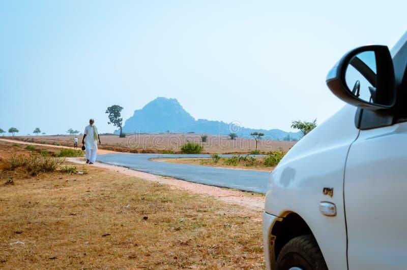 KHANDOLI JHARKHAND, INDIEN - JANUARI 25: Ett ensamt folk som går i tom gata på en solig sommardag Det är en viktig turistsp fotografering för bildbyråer