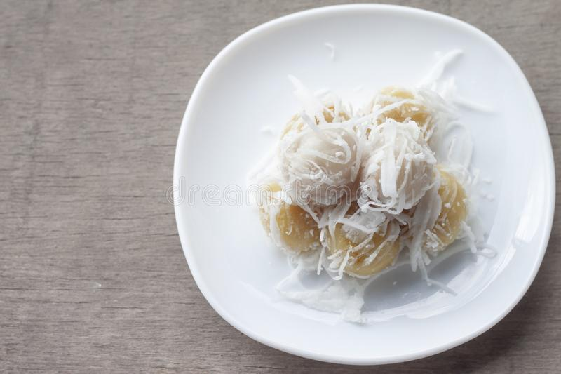 Khanom Tom Kao is Boiled sweets Thai traditional dessert in white plate. Khanom Tom Kao is Boiled sweets Thai traditional dessert in white plate on wooden table stock photography