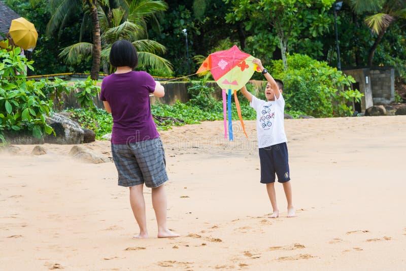 Khaoak, Thailand, 20 juli 2019: De Aziatische jongen en zijn mamma vliegen een vlieger op het strand stock foto