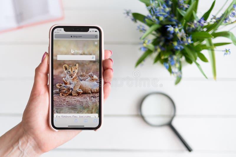 KHARKIV, ΟΥΚΡΑΝΙΑ - 10 Απριλίου 2019: Η γυναίκα κρατά το iPhone Χ της Apple με Bing περιοχή COM στην οθόνη Σελίδα αναζήτησης στοκ φωτογραφίες
